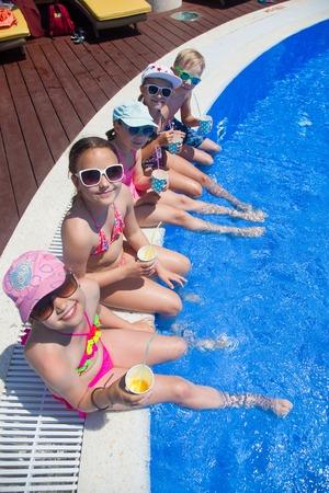actividades recreativas: Los niños beben jugo en el lado de la piscina en el complejo