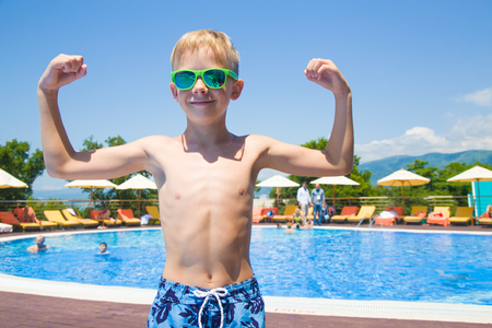 little Boy shows his muscles near the pool Stock Photo