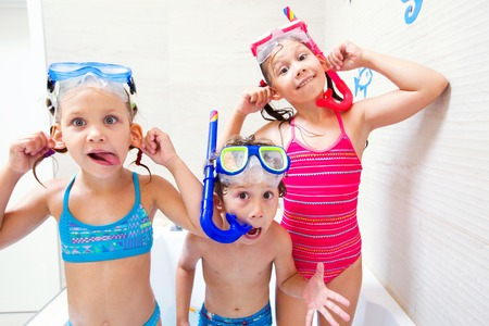 toilet: Little children in swimsuits play in the bathroom like in the sea Stock Photo