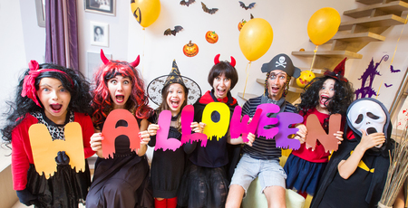big  family in costumes  holds the word Halloween