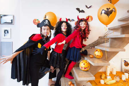 Children riding on a broomstick on a Halloween holiday