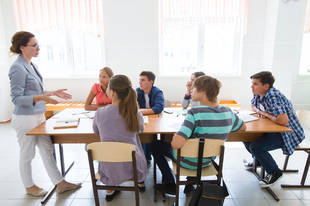 group of students listening to the teacher in the classroom at school