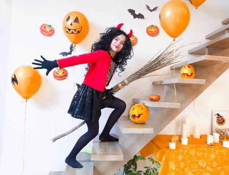 Girl in costume devil on broom to halloween Stock Photo