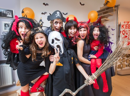 large family in costumes has fun in her house in halloween