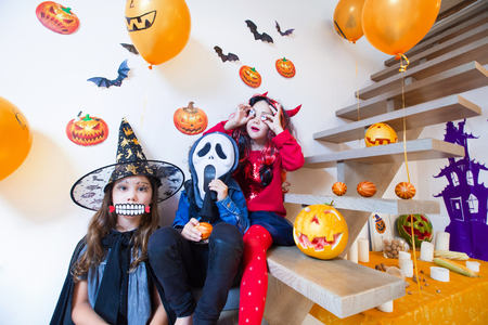 Children in monster costumes have fun on a Halloween holiday