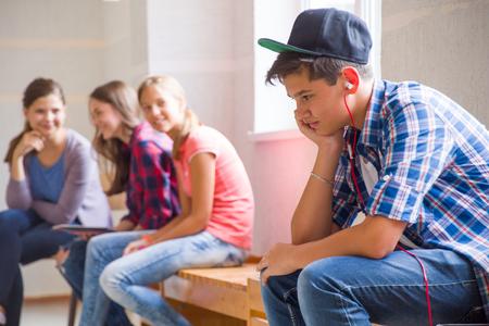 Boy teenager sad alone sitting in school corridor