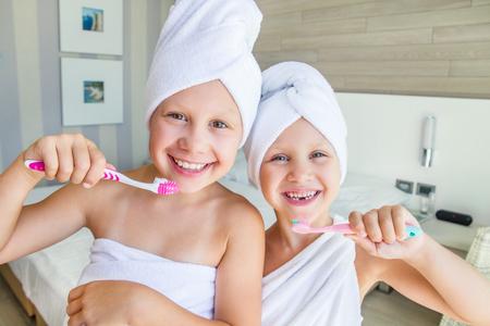 Portrait de deux petite fille dans une serviette se brosser les dents dans la salle de bain Banque d'images - 86275083