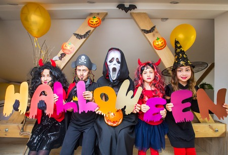 kids in costumes holds the word Halloween