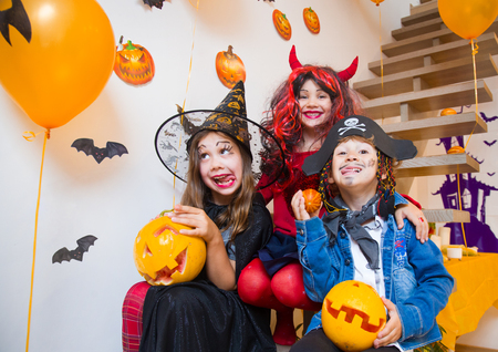 Little kids in  costumes on a Halloween party Stock Photo