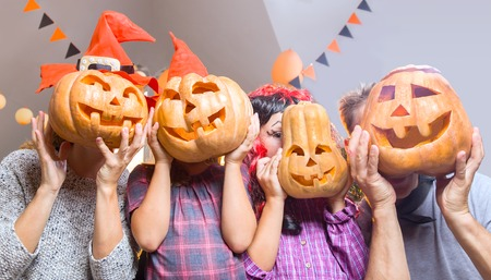 행복 한 가족 집에서 할로윈을 맞는다. 사람들은 머리 대신 호박을 가지고 있습니다. 스톡 콘텐츠