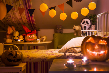 interior of a children's bedroom decorated for  Halloween holiday in the night illumination Stock Photo - 87559781