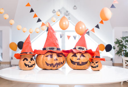 lot of pumpkins with painted faces on a table in a bright apartment Stock Photo