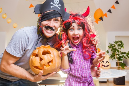 Dad with a little daughter is fooled in  halloween at home.