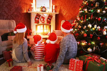 happy family celebrating Christmas near the fireplace under the Christmas tree Banque d'images