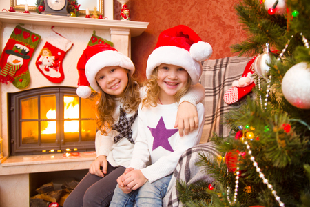 kids celebrating Christmas near the fireplace under the Christmas tree.