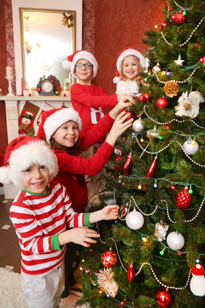Little children decorate the Christmas tree