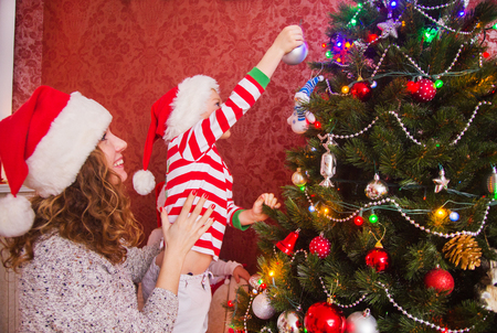 Little child with mother decorate the Christmas tree