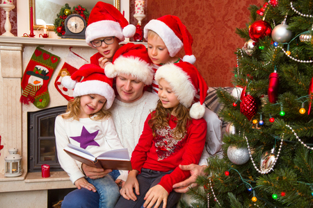 father reads a book to children on Christmas day by the fireplace under the Christmas tree...