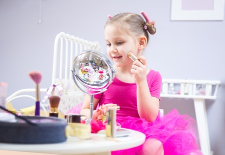 little girl of a fashionista sitting in front of a mirror in a childrens room