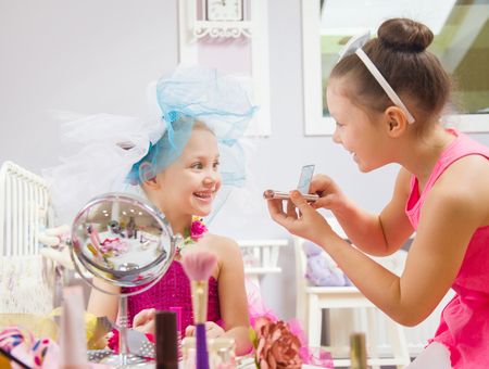 two little girls fashionista  does makeup in a childrens room