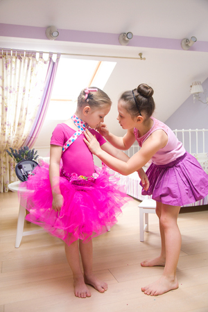 two little girls fashionista dress up in a childrens room