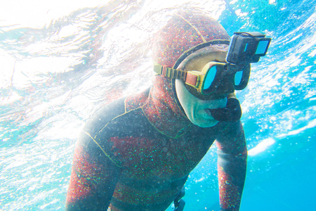 man in  neoprene suit with a camera on  mask dives into the depths of the sea Stock Photo