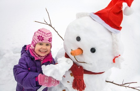little girl  with  big snowman in winter day Stock Photo