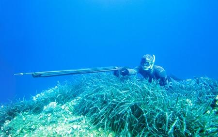 man spearfisher hanting in deep sea