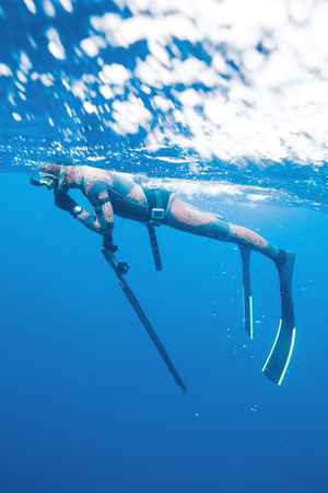 underwater hunter rests on the surface of the sea before diving