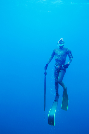 young man in a neoprene suit with a gun dives into the depths of the sea for spearfishing Stock Photo