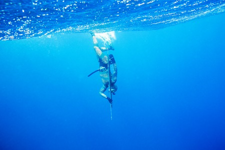 Underwater hunter  with gun dives into the depths of the sea Stock Photo