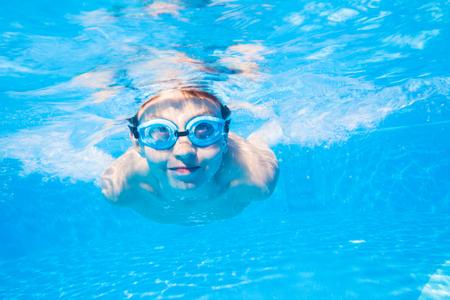 underwater photo of  little boy swimming  in pool