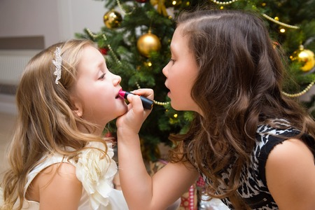 little girls make up on the background of a Christmas tree Stock Photo