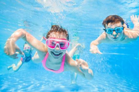 kleine kinderen spelen en zwemmen in het zwembad onder het water. Stockfoto
