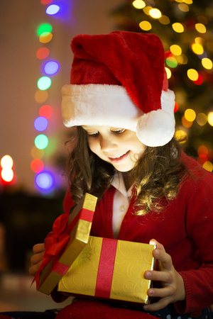 Little girl opening Christmas gift under the Christmas tree
