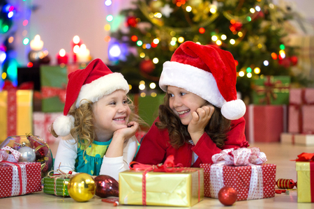 two little girls with presents around the Christmas tree Stock Photo