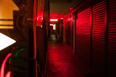 dark street lit by red lanterns in the greenery of the night city Stock Photo