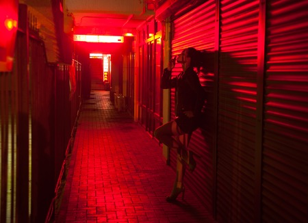 smoking woman leaned against the wall at the red light street at night