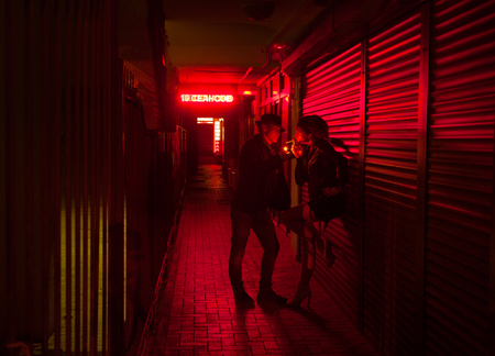 man is lighting a cigarette for a woman at  wall in a street of red lanterns at night