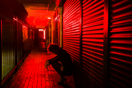 Sad woman crouched by the wall on the street of red lanterns at night