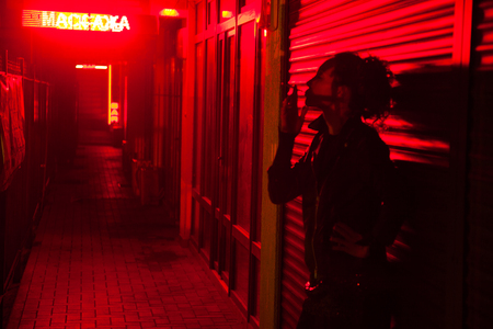Smoking woman leaned against the wall at the red light street at night Stock Photo