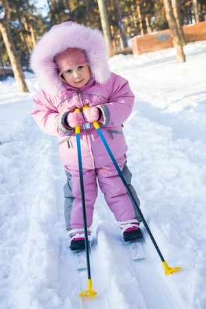 baby with ski poles in the snow making moves in winter park Stock Photo
