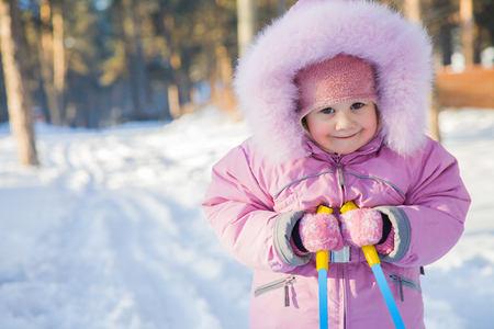 baby with ski poles in the snow making moves in winter park Reklamní fotografie