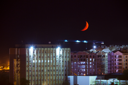 Night Photo of a sickle moon of red color over the city