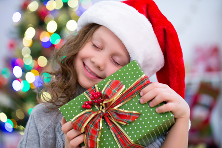 little girl in Santa hat holding a present under the Christmas tree