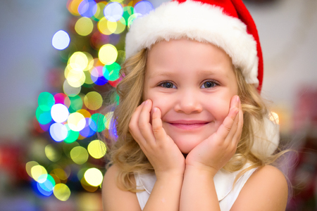 little girl in Santa hat sitting under the Christmas tree
