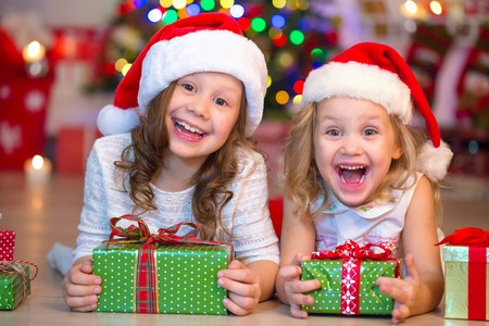 two little girls with presents around the Christmas tree Stockfoto
