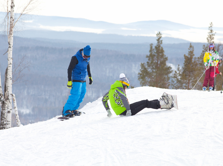 young couple of snowboarders learns to ski in a ski resort Stock Photo