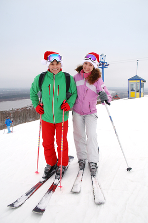 young couple of skiers  in santa cap skiing to ride a ski resort