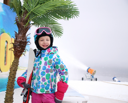 little girl in a ski equipment on the snow near a palm tree Stock Photo